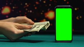 Дама показывая пачку долларов около смартфона с зеленым экраном, применения видеоматериал