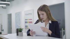 Дама портрета обеспокоеная внимательная молодая в официальных одеждах внимательно проверяя бумаги в положении офиса на сток-видео