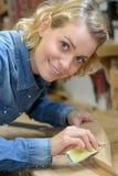 Дама портрета тереть вниз с древесины с бумагой песка Стоковые Изображения