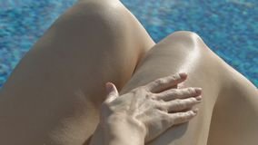 Дама прикладывая лосьон anticellulite к ее ногам, остаткам и спасению на спа-курорте видеоматериал