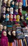 Дама проверяет разнообразие красочных головных платков для продажи в Fez medina, Марокко Стоковое Изображение RF