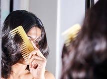 Дама расчесывая ее волосы смотря ее изображение на зеркале стоковое изображение rf