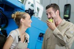 Дама смеясь как мужские укусы коллеги в зеленое яблоко стоковые изображения