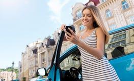 Дама смотря телефон около автомобиля Стоковая Фотография RF
