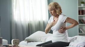 Дама среднего возраста касаясь ее комоду, страдая от сердечного приступа дома, заболевание стоковое изображение rf