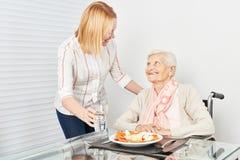 Дама ухода служит еда к старухе стоковые фотографии rf