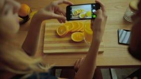 Дама фотографируя вкусные апельсины в кухне сток-видео