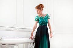 Дама redhead моды молодая милая играя рояль стоковая фотография rf