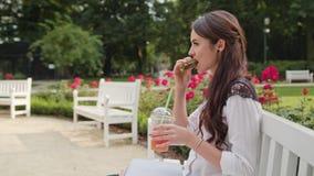 Дама Sitting на стенде в парке и компьтер-книжке использования Стоковое Фото