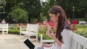 Дама Sitting на стенде в парке и компьтер-книжке использования Стоковая Фотография RF