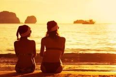 2 дамы в крышках рождества на пляже захода солнца Стоковая Фотография