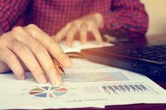 Данные анализируя с ручкой удерживания бизнесмена на диаграммах и диаграмме Стоковая Фотография