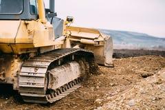 Данные о промышленности - выравнивать бульдозера желтого цвета места строительства дорог и moving почва во время здания шоссе стоковые фото