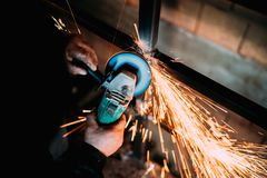 Данные о промышленности конструкции - закройте вверх metalworker используя точильщика диска для инструментального металла стоковые фотографии rf