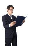 Данные по азиатского бизнесмена читая важные в папке файла, Стоковая Фотография