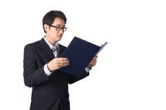 Данные по азиатского бизнесмена читая важные в папке файла, Стоковое Изображение