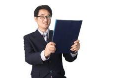 Данные по азиатского бизнесмена читая важные в папке файла, Стоковая Фотография RF