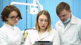 3 дантиста смотрят планшет в медицинском шкафе и диагноз обсуждать, концепция медицины Медицинские профессионалы акции видеоматериалы