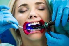 Дантисты вручают работу на пациенте молодой женщины с зубоврачебными инструментами Женский пациент с ранораширителем на дантисте стоковые фото
