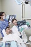 Дантисты объясняя отчет о рентгеновского снимка к пациенту стоковые фотографии rf