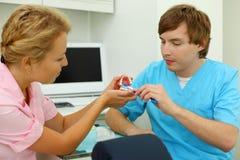 Дантисты показывают как правильно почистить зубы щеткой Стоковые Изображения
