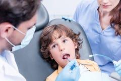Дантисты рассматривая зубы мальчика Стоковое фото RF