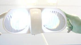 Дантист включает и регулирует свет для быстрой проверки зубов сток-видео