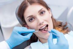 Дантист в защитных перчатках рассматривая зубы молодой женщины Стоковые Фото
