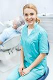 Дантист в медицинской форме сидя в клинике и усмехаясь на камере Стоковое Изображение RF
