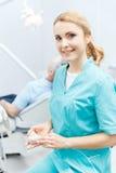Дантист в медицинской форме сидя в клинике и усмехаясь на камере Стоковое Фото