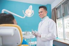 Дантист говоря к его пациенту зубоврачебной заботы стоковые фотографии rf