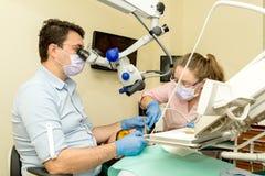Дантист делая зубоврачебную обработку используя микроскоп стоковые фото