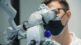 Дантист используя микроскоп видеоматериал
