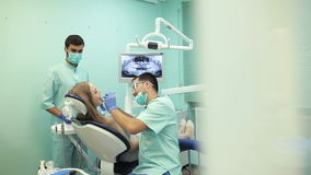 Дантист используя зубоврачебную леча УЛЬТРАФИОЛЕТОВУЮ лампу на зубах пациента сток-видео