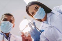 Дантист и ассистент держа зубоврачебные инструменты стоковая фотография