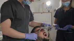 Дантист и его ассистентская сторона пользы обхватывают пока обрабатывающ терпеливые зубы ` s Размещение верхней челюсти по отноше сток-видео