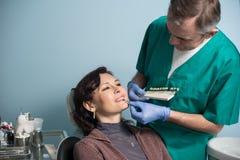 Дантист и женский пациент проверяя и выбирая цвет зубов в зубоврачебном офисе клиники зубоврачевание стоковые фотографии rf