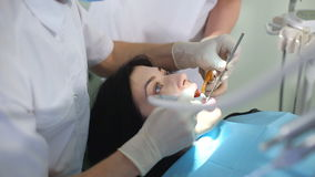 Дантист и медсестра начинают обработку в зубоврачебном офисе сток-видео