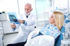 Дантист и пациент рассматривают необходимые обработки teet Стоковые Изображения RF
