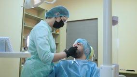 Дантист молодой женщины на работе в офисе с пациентом Стоковые Изображения