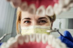 Дантист над открытым терпеливым ртом ` s смотря в зубах Устная забота I стоковая фотография rf