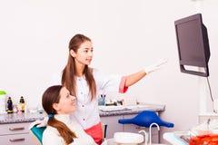 Дантист показывает женскому пациенту рентгеновский снимок стоковое изображение