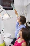 Дантист показывая девушке цифровое изображение зубов и камедей Стоковые Фото