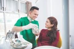 Дантист показывая зубоврачебную модель челюсти стоковое изображение