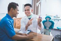Дантист показывая зубоврачебную модель челюсти Стоковые Фотографии RF