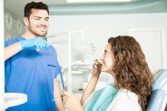 Дантист показывая метод чистить зубы щеткой к пациенту в клинике стоковое фото