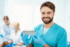 Дантист представляет с масштабом цвета зуба На фоне его коллег, они обрабатывают маленькую девочку Стоковая Фотография RF