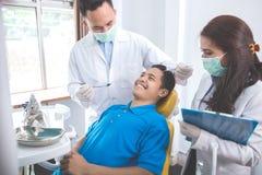 Дантист проверяя терпеливые зубы стоковая фотография