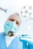 Дантист профессионала зрелый в медицинской маске держа зеркало рта Стоковые Изображения