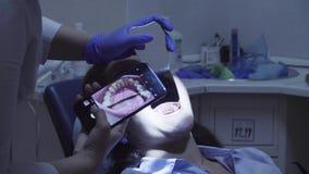 Дантист снимая терпеливые зубы ` s в зеркале акции видеоматериалы